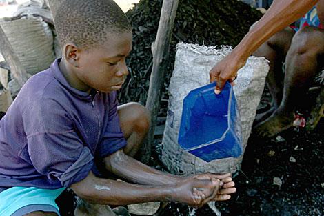Un niño haitiano lavandose las manos. | AFP