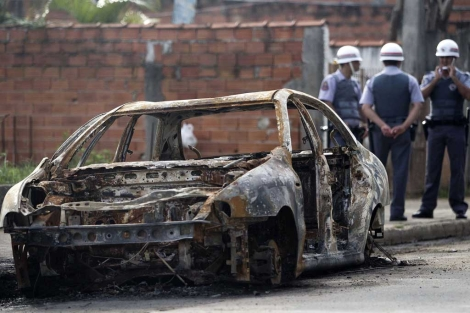 La policía junto a un coche quemado durante el desalojo. Reuters