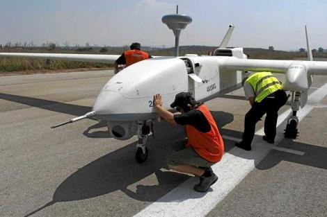 Varios operarios reparan un avión sin piloto.| Reuters