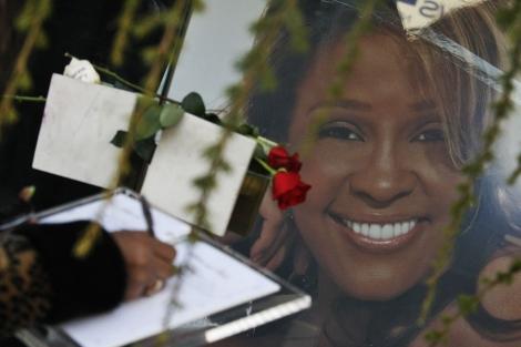Una mujer deja un mensaje en el libro del funeral de la cantante. | Reuters