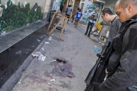 Dos agentes ante la escena del crimen en la favela Nova Holanda.| Afp