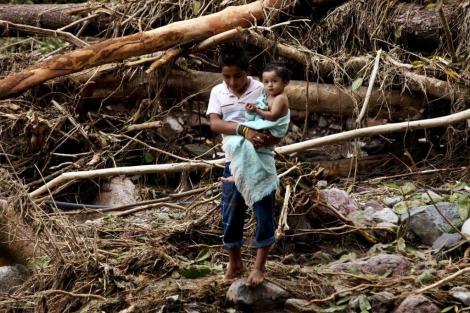 Un niño cruza una zona afectada con su hermana en brazos. | Reuters
