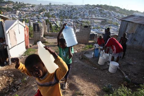Unos niños cargan con bidones en un campo de desplazados. | Unicef