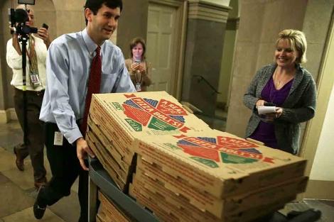 Un empleado trae pizzas en el Capitolio durante las negociaciones. | Afp
