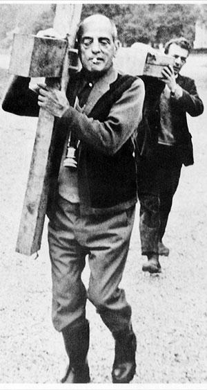 Buñuel ayuda a cargar una cruz en el rodaje de 'La Vía Láctea'.