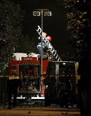 Unos bomberos despliegan una escalera en el lugar. (Foto: EFE)