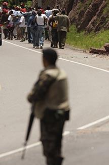 Partidarios de Zelaya se alejan de los soldados que detuvieron su bus. | AP