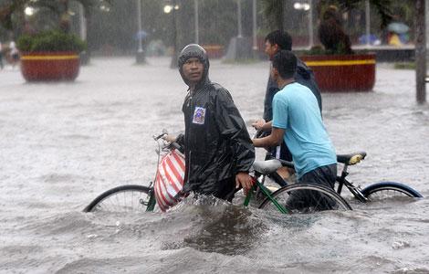 Dos hombres intentan cruzar una calle inundada en Manila. | Efe