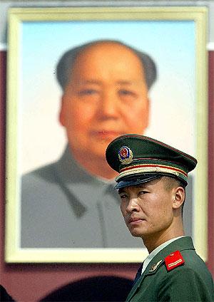 Un policía chino en la Plaza de Tiananmen, bajo un retrato de Mao. | F. Brown