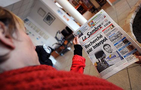 Una mujer lee la noticia de la búsqueda de Rwamucyo en un periódico de Maubeuge. | AFP