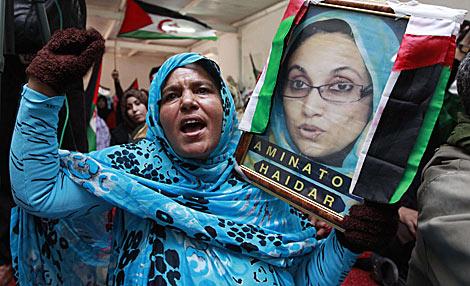 Una refugiada saharaui protesta con un retrato de Haidar. | Reuters
