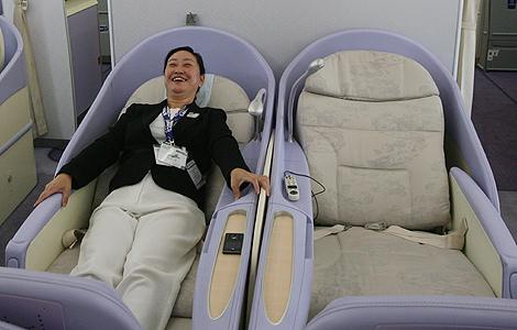 Una mujer prueba un asiento en 'primera' en un nuevo airbus A380, en Shangai.| AFP