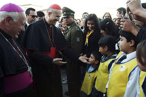 El cardenal Bertone saluda a unos niños tras una misa en  Talcahuano. | Reuters
