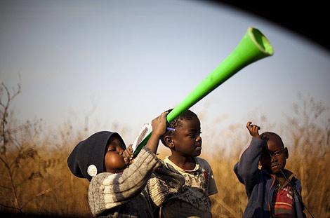 Unos niños tocan la vuvuzela en las afueras de Johannesburgo. | Emilio Morenatti