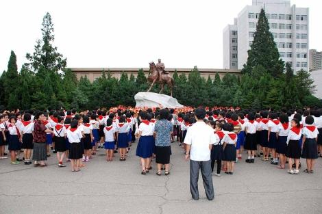 Escolares frente a una estatua de Kim Jong Il. | David Jiménez