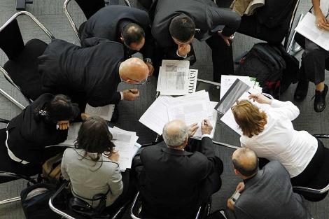 Varios delegados revisan algunos documentos durante la cumbre. |  AP