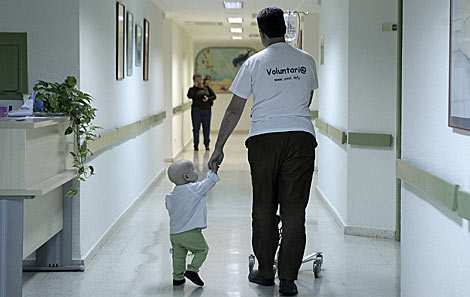 Un voluntario cuida de un niño enfermo en un hospital de Málaga. | Antonio Heredia