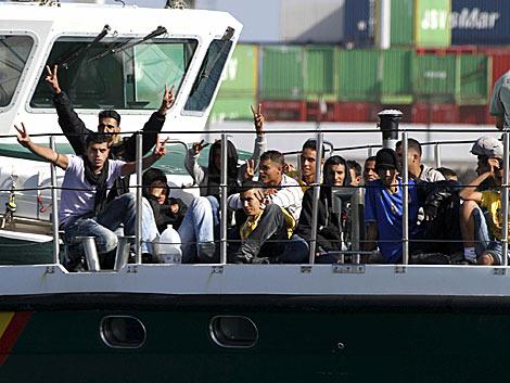 Algunos inmigrantes hacen gestos de victoria al llegar a puerto. | Efe