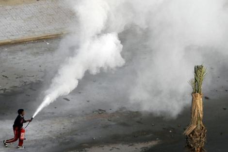 Un manifestante utiliza un extintor en las protestas en Suez. | Reuters