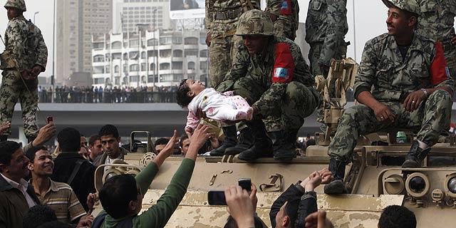 Un soldado sujeta a bebé durante las protestas de ayer en El Cairo. | Reuters