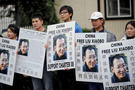 Activistas chinos exhiben carteles en apoyo del encarcelado Liu Xiaobo | Afp