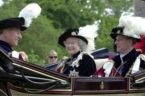La reina de Inglaterra rodeada por el príncipe de Gales y el principe de Edimburgo. | AFP