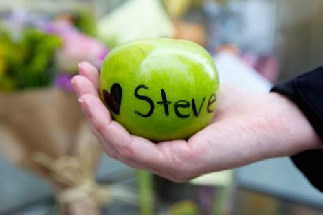 Una mujer sostiene una manzana con una dedicatoria a Steve Jobs, en California. | Reuters
