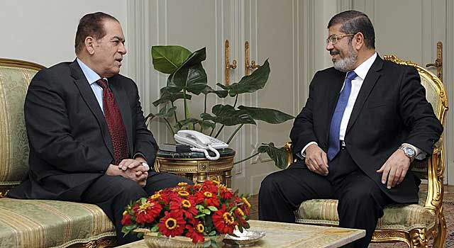 El presidente de Egipto, Mohamed Mursi, habla con el primer ministro, Kamal Ganzouri. | Reuters