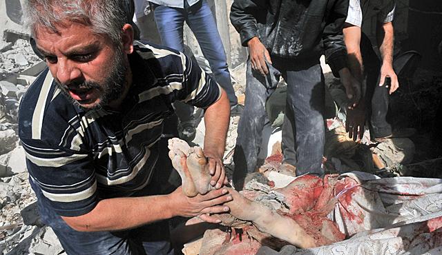 Un hombre mueve el cadáver de un niño, atrapado entre los escombros, tras el bombardeo. | Afp
