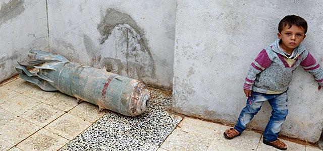 Un niño, junto a un artefacto desactivado en Taftanaz, en la provincia de Idlib.| Afp