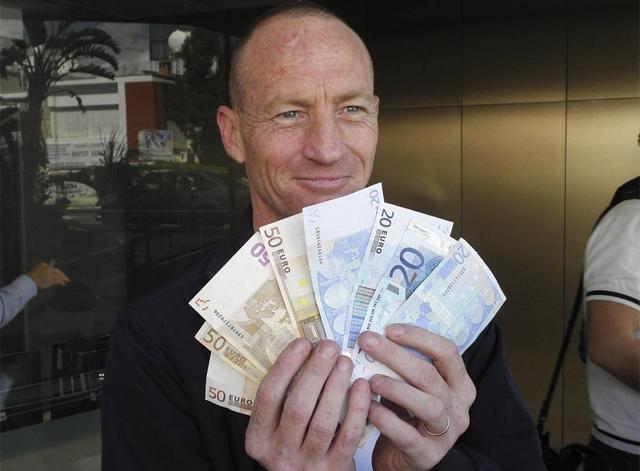 Un chipriota enseña los ahorros que ha podido retirar del banco. | Efe