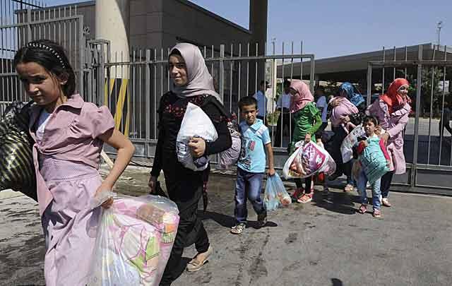 Refugiados sirios cruzando la frontera con Turquía.   Efe