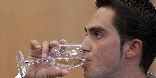 Alberto Contador bebe durante su conferencia de prensa. (Efe)