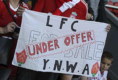 Aficionados del Liverpool muestran una pancarta que dice algo así como: 'El Liverpool, de rebajas'. | Efe