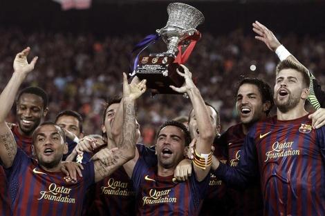 Los jugadores del Barcelona levantan el trofeo de la edición de 2011. EFE