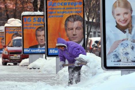 Una limpiadora ante carteles electorales de Viktor Yushchenko y Yulia Tymoshenko.| Afp