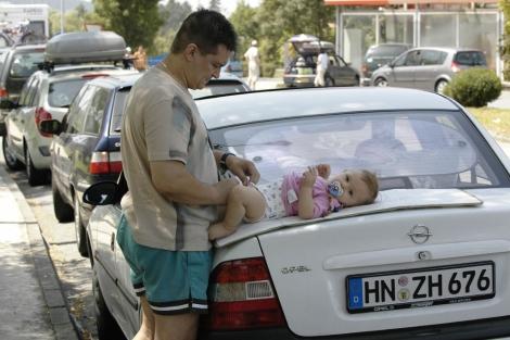 Un hombre cambia el pañal a su hijo encima del maletero del coche. | Javier Zorrilla