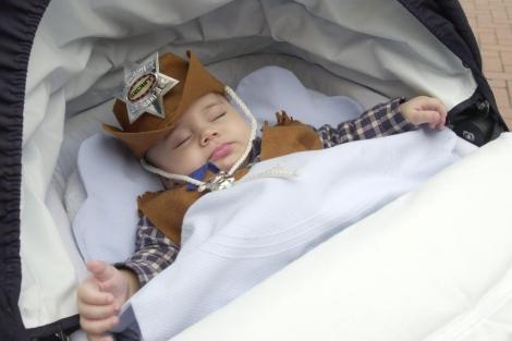Un bebé durmiendo en su cochecito durante el carnaval de Valladolid. | Carlos Arranz.