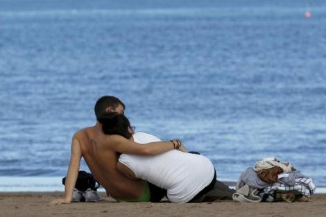 Una pareja en la playa. | Efe | Kai Rosterlin.