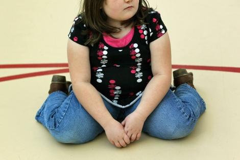 Una niña sentada en el gimnasio de su colegio. | Foto: John Moore
