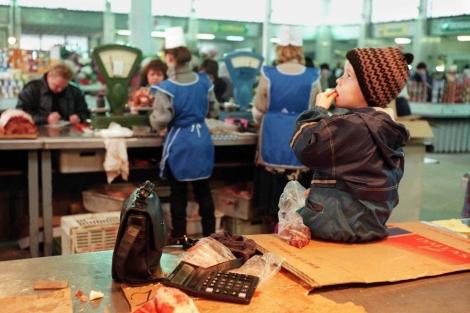 Un niño come mientras su madre acaba de trabajar en un mercado. | AP
