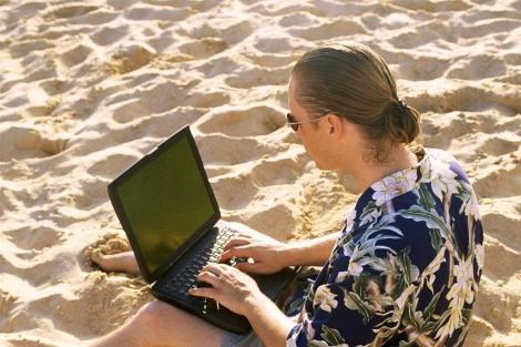 Un hombre consulta el portátil en la playa.| Afp