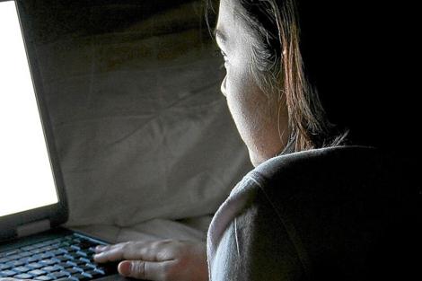 Una joven consulta su ordenador portátil.| D.F