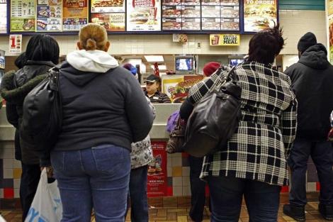 Gente haciendo cola en un local de comida rápida.| Reuters