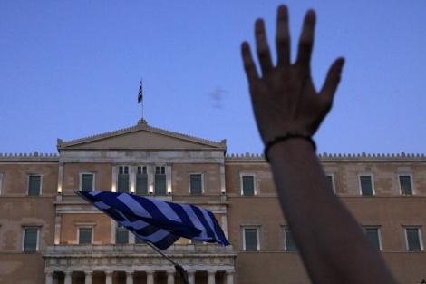 Un manifestante alza su mano ante el Parlamento griego. | Reuters