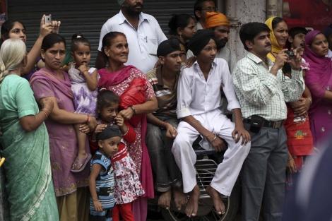 Varias jóvenes indias observan una fiesta religiosa.   AP