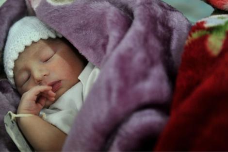 Un recién nacido duerme en su cuna. | Adek Berry