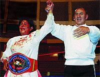 """Carmen Rosa –con sangre propia en su rostro y de sus contrincantes en la ropa– recibe el cinturón oficial que la identifica como """"Campeona de los Titanes del Ring""""."""