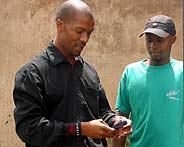 Un comercial de la banca Wizzit da explicaciones con un m?vil a un posible cliente en el suburbio de Soweto (Foto: REUTERS)